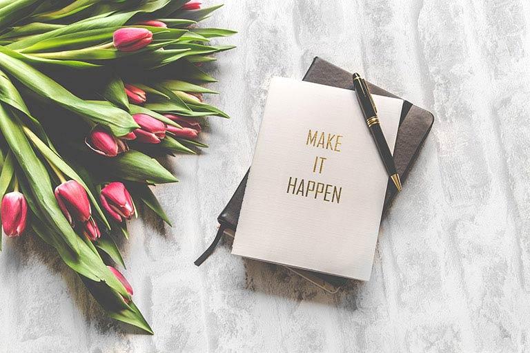 """tulipes à côté d'un carnet noir et d'une carte """"Make it happen"""""""